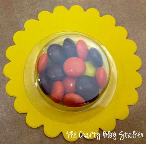 adhere the treat cup to the yellow scallop circle