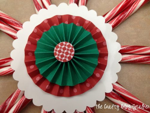 Give the perfect gift this holiday season, a Candy Cane Wreath! It's edible seasonal Christmas Decor. An easy DIY craft tutorial idea.