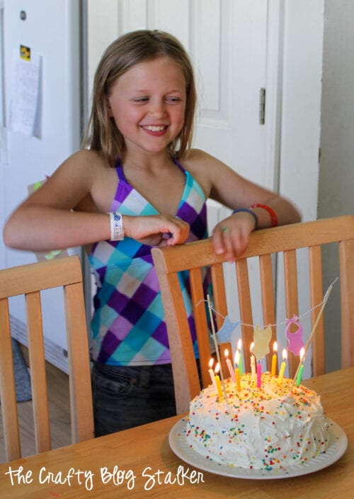 a girl about to blow out the candles on her birthday cake