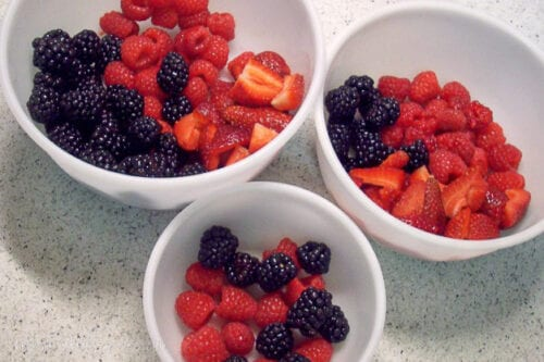 strawberries, raspberries, and blueberries divided into 3 bowls