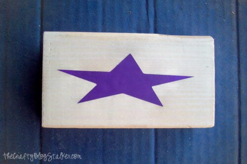 a vinyl star placed on a piece of wood to be used ads a stencil