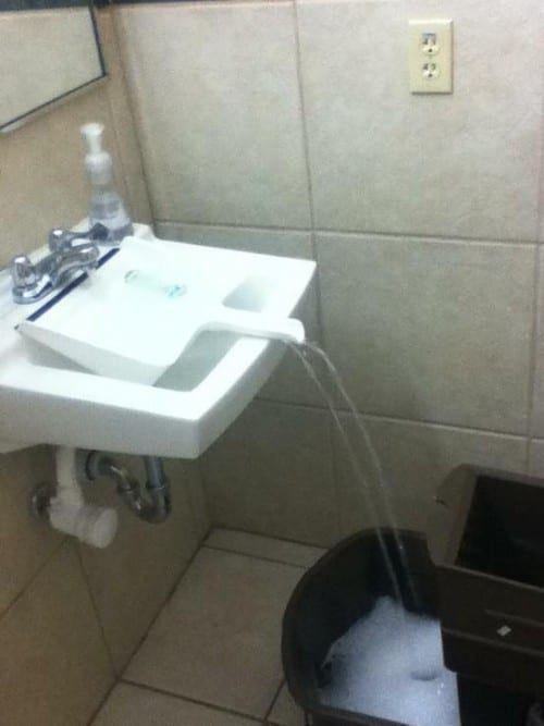 dustpan laid across a sink to get the water to a larger bucket on the floor - cleaning tips