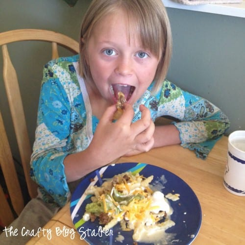 How to Make Delicious Taco Meat Loaded Fries featured by top US craft blog, The Crafty Blog Stalker: child eating