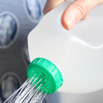 pouring water out of a milk jug with holes poked in the lid - tips for the home