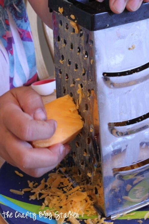 image of a child grating cheese