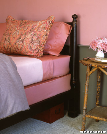 a pink bed made with pillows and sheets with a fitted sheet on the box spring mattress