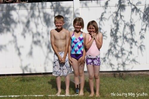 three kids standing in the sprinkler