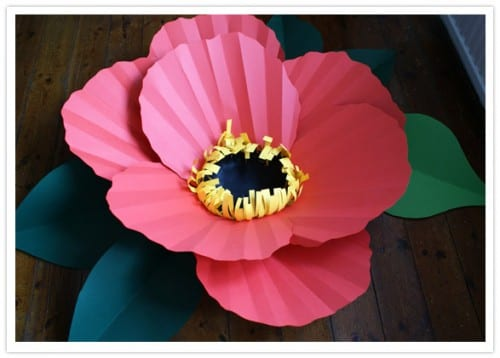 large pink, yellow and black paper flower with green paper leaves
