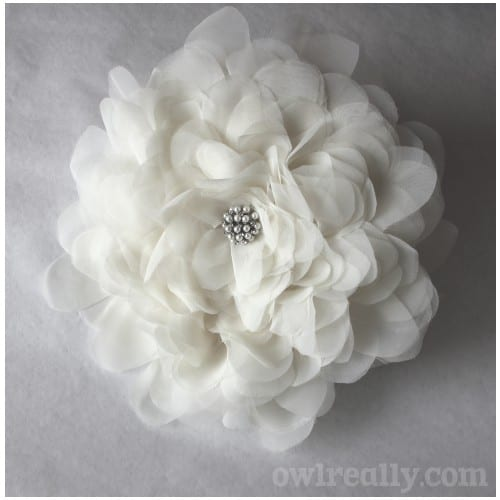 20 Beautiful Fabric Flowers Tutorials, a roundup of fabric flowers featured by top US craft blog, The Crafty Blog Stalker: a close up of a white giant single bloom with pearls in the middle