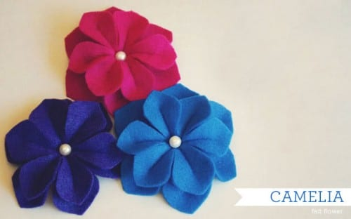 20 Beautiful Fabric Flowers Tutorials, a roundup of fabric flowers featured by top US craft blog, The Crafty Blog Stalker: close up of three felt camelia handmade flowers