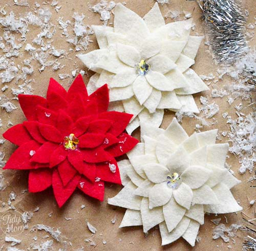 20 Beautiful Fabric Flowers Tutorials, a roundup of fabric flowers featured by top US craft blog, The Crafty Blog Stalker: a close up of three felt poinsettias two white one red