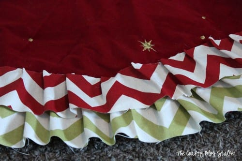 gluing strips of fabric onto a tree skirt base to create a new tree skirt
