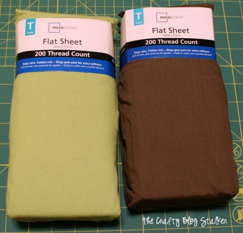a green flat sheet and brown flat sheet new in package to use for the quilting fabric