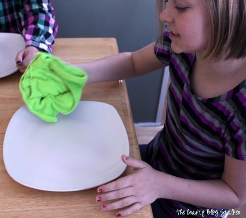 a young girl cleaning the white ceramic plate with isopropyl alcohol and a green rag