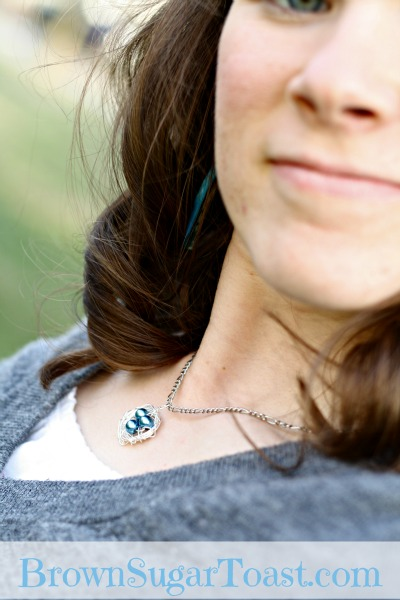 a woman wearing the mama bird nest necklace