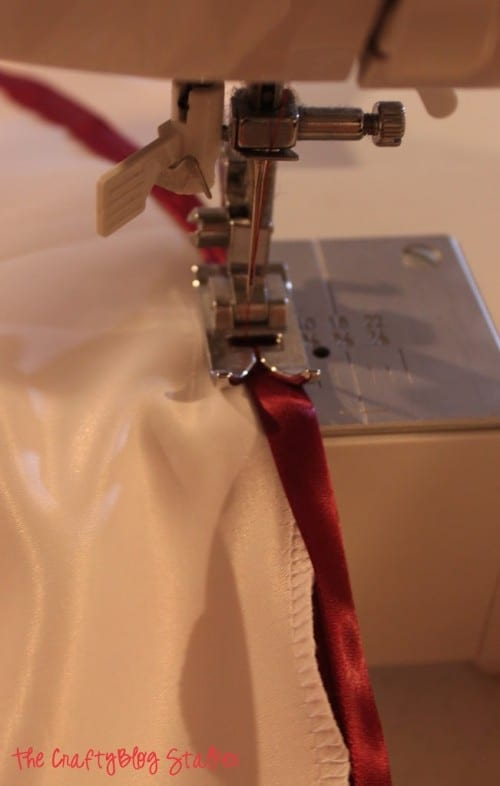 sewing the satin bias tape over the serger sewn edge