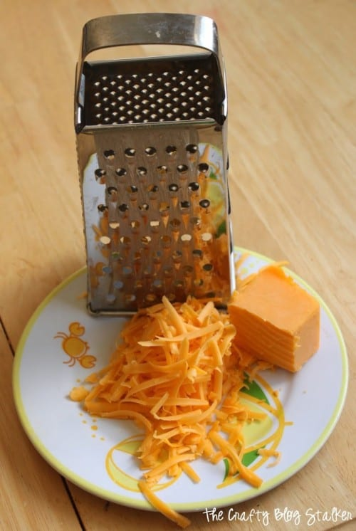 image of cheese grater with shredded chees