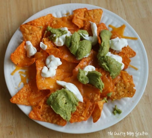image of a place of quick and easy nachos with Doritos, melted shredded cheese, sour cream and wholly guacamole