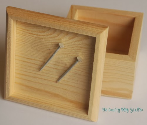 a wood box with 2 nails
