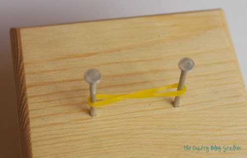 a yellow rubber band twisted in a figure 8 over 2 nails