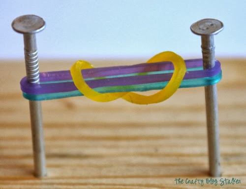 a yellow rubber band pulled over 2 rubber bands