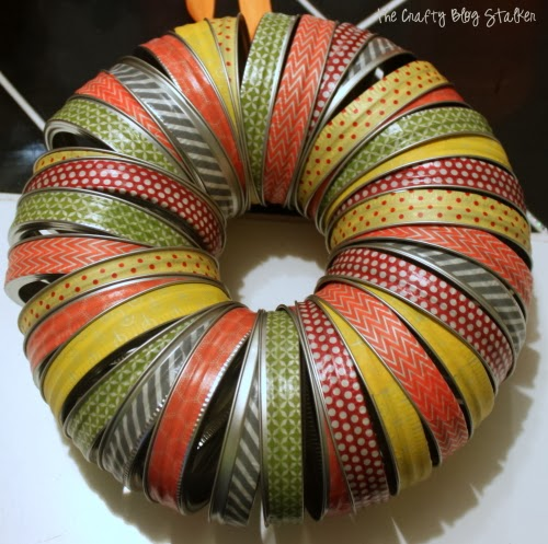 Create a Canning Lid Wreath out of Mason Jar Lids and Washi Tape. An easy DIY craft tutorial idea that can be made to match any season.