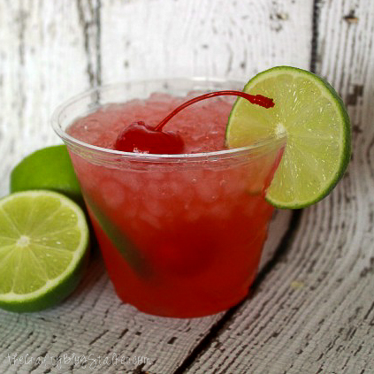 a cup of cherry limeade with a lime garnish