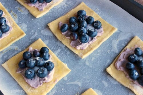 blueberries and blueberry cream cheese on puff pastry sheets