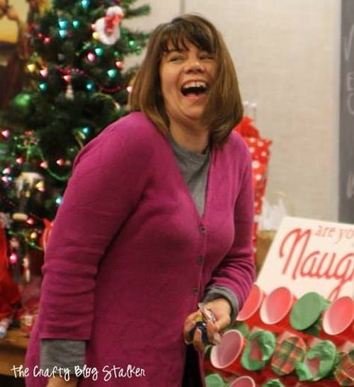 a girl laughing as she plays the naughty or nice Christmas game at a Christmas party
