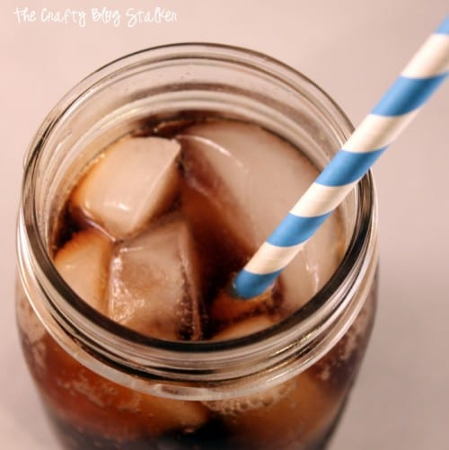 top view of a glass of dirty dike soda with ice and a blue and white striped straw