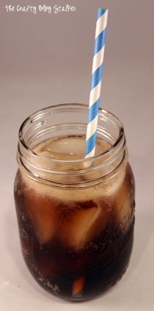 a glass of dirty dike soda with ice and a blue and white striped straw