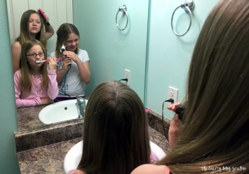 three girls getting ready in the morning in front of a bathroom mirror