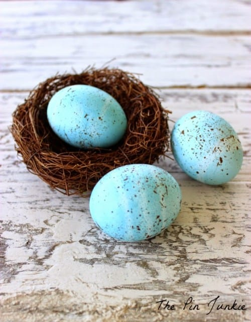 three blue speckled eggs, a small nest on a white wood background
