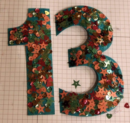 the number 13 cut out of blue cardstock and covered in glitter and sequins