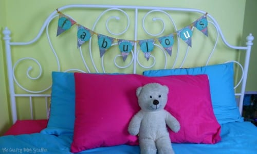 fabulous paper pennant banner hanging on a white metal headboard