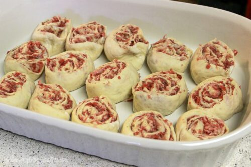 a casserole baking dish with uncooked sausage rolls