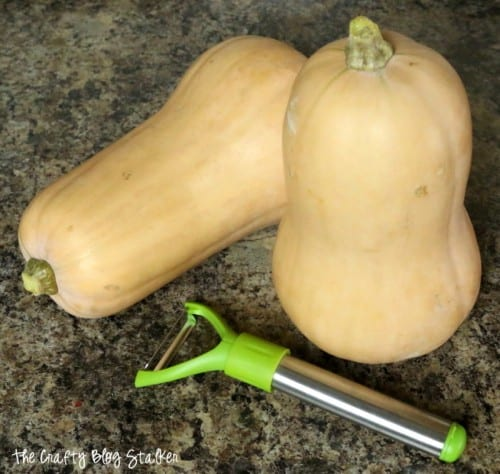 two butternut squash and a vegetable peeler