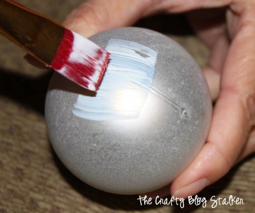 applying mod podge to a plastic ornament