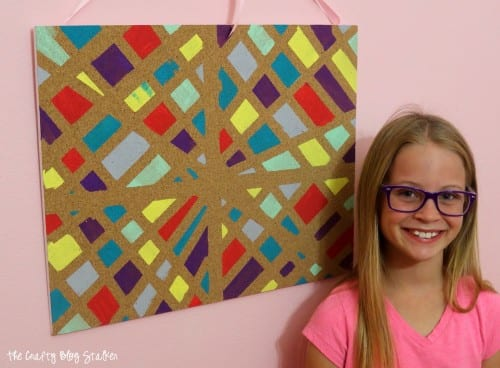 image of the finished painted cork board with the young girl artist