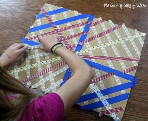 image of a girl decorating a cork board with strips of washi tape