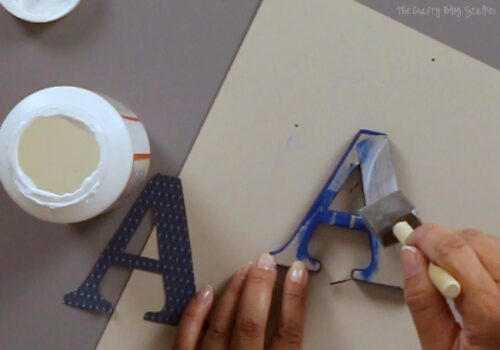 applying mod podge to the front of the monogram letter