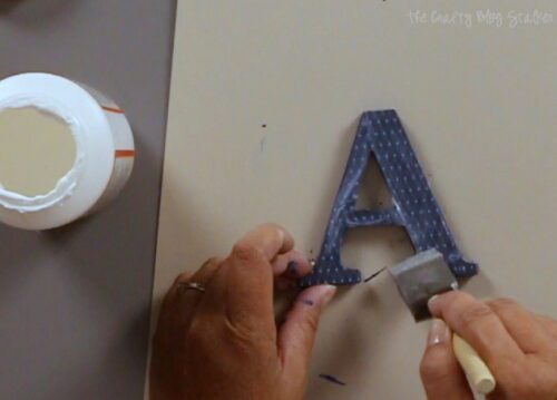 applying mod podge over the top of the letter