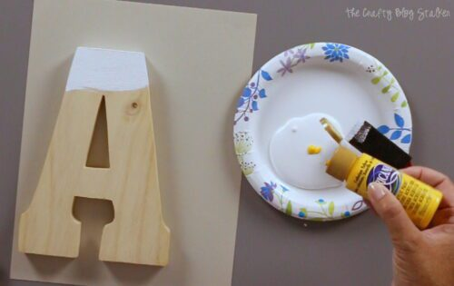add a few drops of yellow paint to gesso