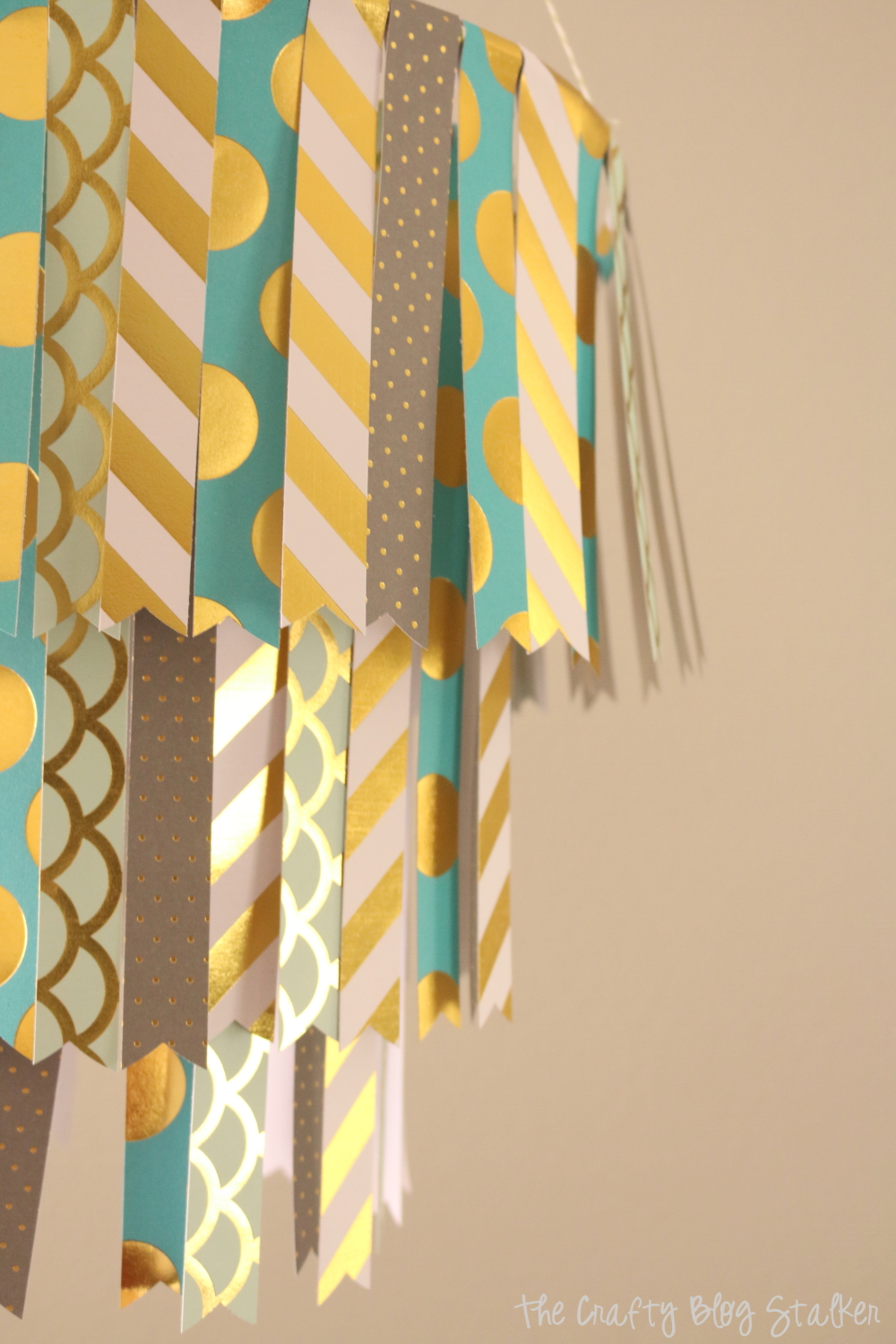 Create a fun DIY Hanging Paper Mobile by following this simple tutorial. Use your favorite pattern paper to match your home decor or party decor.