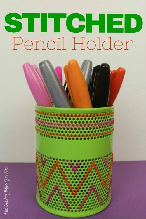 a green metal pencil holder that has been stitched with orange and pink DMC floss