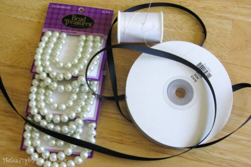 perlas, cinta negra, hilo de coser y una aguja
