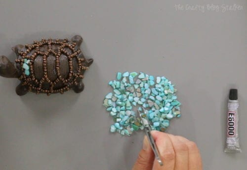 using craft tweezers to grab crushed shell pieces