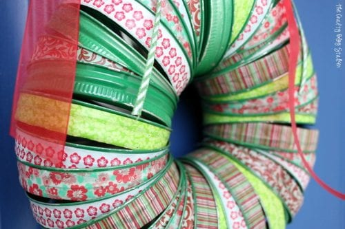 Learn how to make make a canning lid Christmas wreath for the front door. Use washi tape with this easy DIY craft tutorial idea perfect for the holidays.