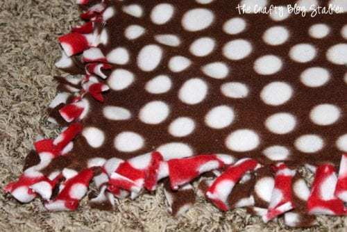 Make a tied fleece blanket that is perfect to snuggle and keep you warm. An easy DIY craft tutorial idea that also makes a great handmade gift!