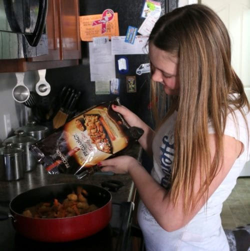 girl pouring P.F. Chang's Home Menu frozen meal into a pan to make for dinner